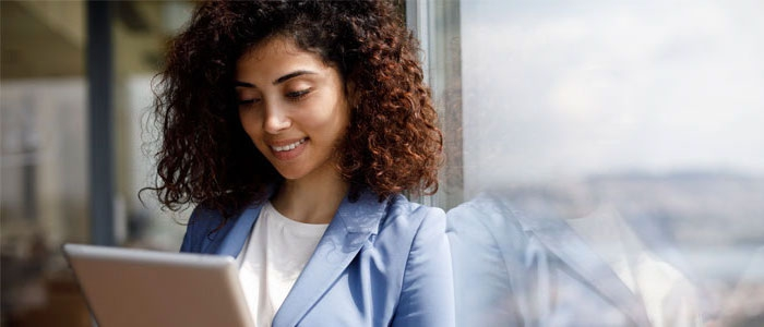 A woman smiles while reading content on her laptop computer.