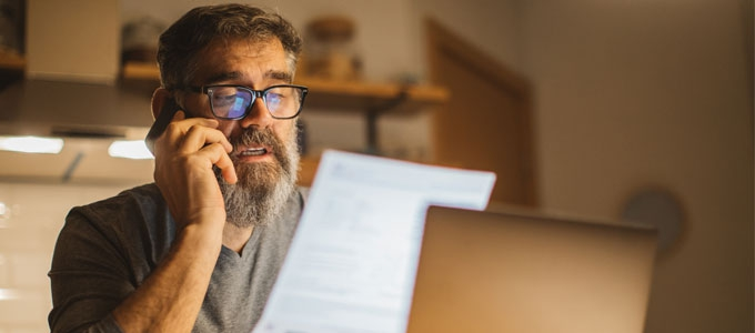 A man talks on a phone while looking at a document.