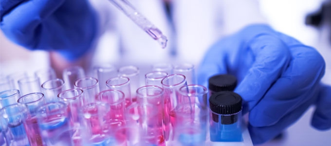 A researcher handles vials in a lab.