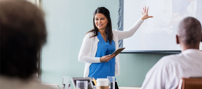 A woman conducts a presentation using a white board.