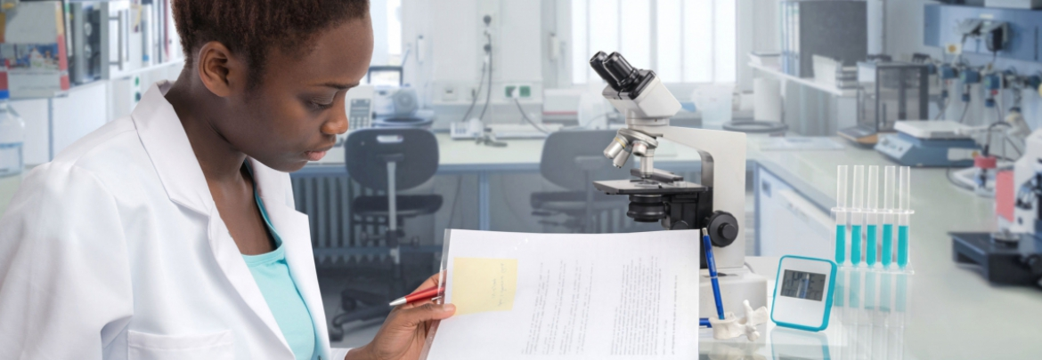 A female researcher looks over documents in a lab.