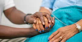 A caregiver holds the hand of a patient.